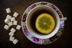 Geurige thee met een plak van citroen in een heldere roze mok, naast dertien suikerkubussen van geraffineerde suiker Royalty-vrije Stock Afbeeldingen