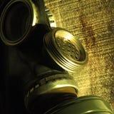 Gevaar Een zwart gasmasker met een membraan voor gesprekken rust op houten raad in helder hard licht Militair concept een eme stock afbeeldingen