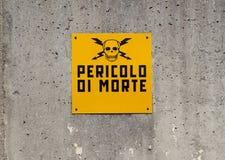 Gevaar van doodsteken, in Italiaans, door een schedel met twee gekruiste bliksem op een concrete muur wordt afgeschilderd die royalty-vrije stock fotografie