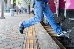 Gevaar, van een trein wordt gehangen, die omhoog de trein in een spitsuur lopen aan het werk, Haasttijd, vakantievakantie, Reisco stock afbeelding