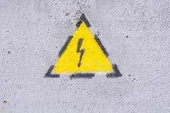 Gevaar van elektrocutie geel teken op geschilderde muur Hoogspanningswaarschuwingsbord stock afbeelding