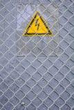 Gevaar van elektrocutie geel teken op grijs Hoogspanningswaarschuwingsbord stock fotografie