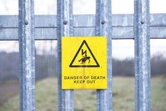 Gevaar van het teken van de doodsveiligheid op houten telegraafpost tegen blauwe hemel stock foto