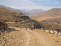 Gevaarlijke en curvy berglandweg met steile daling aan de vallei, Lesotho, Zuid-Afrika stock afbeeldingen