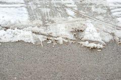 Gevaarlijke en gladde die asfaltweg met gesmolten sneeuw in de wintertijd met de sporen van autobanden wordt behandeld royalty-vrije stock afbeeldingen