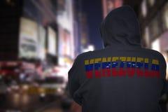 Gevaarlijke mens die zich op een stadsstraat bevinden met zwarte hoodie met tekst Venezuela op zijn rug stock afbeelding