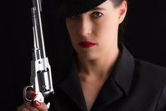 Gevaarlijke vrouw in zwarte met zilveren pistool Stock Foto
