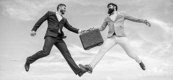 Geval met verhoging uw zaken Succesvolle transactie tussen zakenlieden Aktentasoverdracht in hemel blauwe hemel stock afbeelding