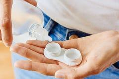 Geval voor contactlenzen en fles met oplossing in vrouwenhanden Eyewear, zicht en visie, oogzorg en gezondheid, oftalmologie royalty-vrije stock foto's