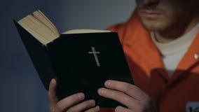 Gevangene die in handcuffs heilige bijbel, berouw voor zonden, geloof en hoop lezen stock footage