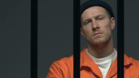 Gevangene die met littekens op gezicht met vertrouwen op camera achter celbars kijken stock video