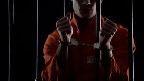 Gevangene die in oranje eenvormige tonende handcuffs, boos en teleurgesteld kijken royalty-vrije stock afbeeldingen