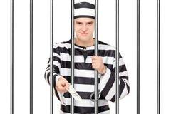 Gevangene die steekpenning achter de tralies aanbieden aan iemand royalty-vrije stock afbeelding
