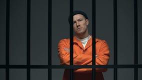 Gevangengenomen gevaarlijke mannelijke misdadiger die handen op borst kruist, die direct eruit ziet stock videobeelden