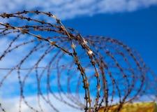 gevangenis De Abstracte illustratie van het prikkeldraad Prikkeldraad op blauwe hemelachtergrond met witte wolken Draadboom Milit stock foto's