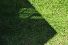 Geveltop met venster gietende schaduw op gazon stock afbeeldingen