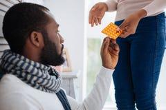 Gevend houdend van meisje die een pakket van pillen geven stock foto's