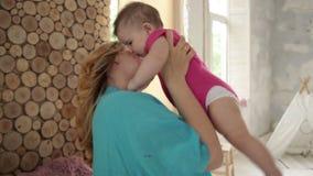 Gevend mamma die haar aanbiddelijk babymeisje kussen stock video