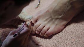 Gevend om de pedicure van meisjesbenen, poetsmiddel, mooie lichten Pedicures in de salon De hoofdzorgen voor de spijkers stock videobeelden