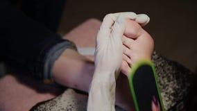 Gevend om de pedicure van meisjesbenen, poetsmiddel, mooie lichten Pedicures in de salon De hoofdzorgen voor de spijkers stock footage