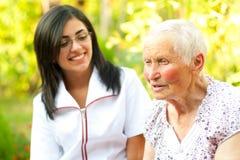 Gevende arts die aan oude dame luistert stock fotografie