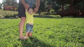 Gevende de zuigelingsjongen van het vaderonderwijs om op gras te lopen stock video