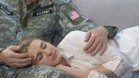 Gevende echtgenoot in het militaire eenvormige het strijken gezicht van de slaapvrouw, paar in liefde stock videobeelden