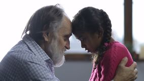 Gevende grootvader die zijn klein droevig meisje troosten stock footage