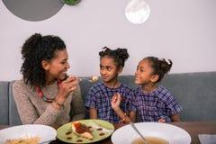 Gevende houdende van krullende moeder die wat kaastaart haar leuke meisjes geven royalty-vrije stock afbeelding