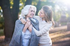 Gevende jonge vrouw die verouderde moeder in openlucht omvatten met deken royalty-vrije stock foto