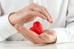 Gevende mens die een rood hart in zijn handen tot een kom vormen Stock Foto's