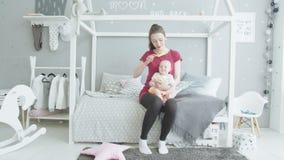 Gevende moeder borstelende baby in de ruimte van kinderen stock videobeelden