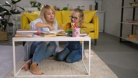 Gevende moeder die haar dochter met thuiswerk helpen stock footage