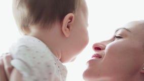 Gevende moeder die met gelukkig weinig baby, kussen en glimlachen spelen stock videobeelden