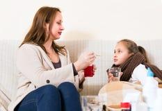 Gevende moeder die zieke dochter verzorgen Stock Fotografie