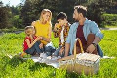 Gevende ouders die picknick met hun jonge geitjes hebben royalty-vrije stock afbeelding