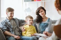 Gevende ouders en zich slecht gedragende jongen tijdens therapiezitting met adviseur stock foto