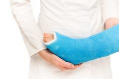 Gevende verpleegster die weinig gebroken been van kind behandelen Stock Afbeeldingen