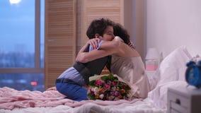 Gevende zoon die bloemen voorstellen aan moeder in bed stock video