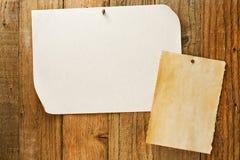 Het gevlekte beige document naled aan verontruste houten muur Stock Foto
