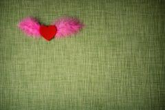 Gevoeld hart en geverfte vogelveren op stoffenachtergrond Stock Afbeeldingen