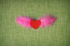 Gevoeld hart en geverfte vogelveren op stoffenachtergrond Royalty-vrije Stock Foto's