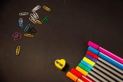 Gevoelde pennen met paperclippen op een zwarte achtergrond stock foto