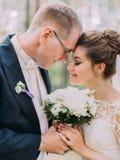 Gevoelig portret van de enkel gehuwde status hoofd-aan-hoofd terwijl het houden van het wedboeket royalty-vrije stock afbeelding
