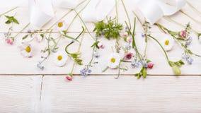 Gevoelige witte, blauwe, roze bloemen en wit lint op witte houten raad De lucht hoogste vlakke mening, legt De ruimte van het exe Royalty-vrije Stock Afbeelding