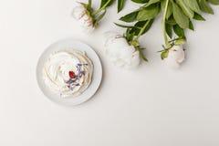 Gevoelige witte pioenen en cake op een witte achtergrond stock foto's