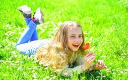 Gevoeligheidsconcept Het kind geniet de lente van zonnige dag terwijl het liggen bij weide met madeliefjebloemen Het meisje op he royalty-vrije stock foto's