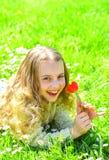 Gevoeligheidsconcept Meisje die op gras, grassplot op achtergrond liggen Het meisje op het glimlachen gezicht houdt rode tulpenbl stock afbeeldingen