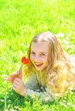 Gevoeligheidsconcept Meisje die op gras, grassplot op achtergrond liggen Het meisje op het glimlachen gezicht houdt rode tulpenbl royalty-vrije stock afbeeldingen