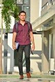 Gevoelloze Jeugdige Filipijnse Student With Books Walking op Campus royalty-vrije stock afbeeldingen